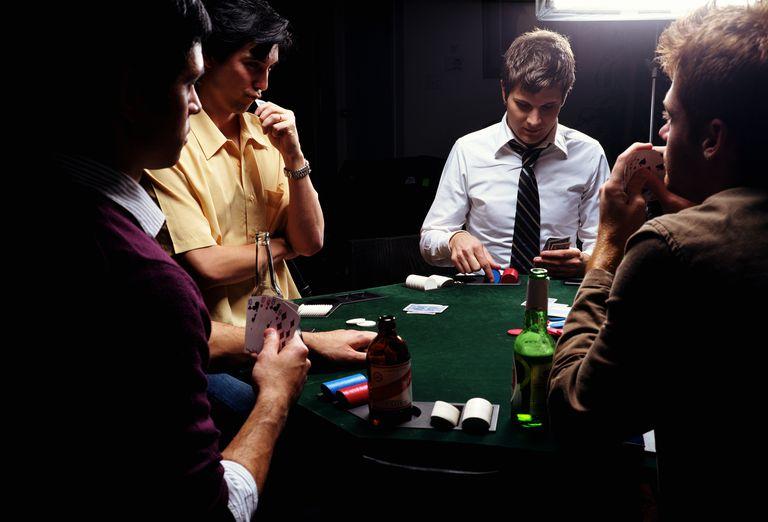 Men playing poker, young man selecting chips