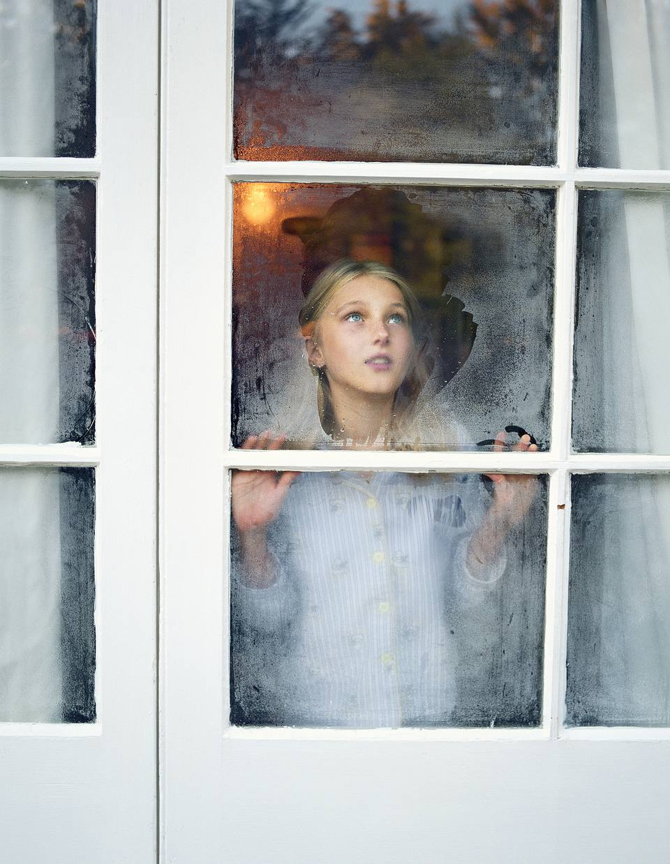 Girl looking out foggy window