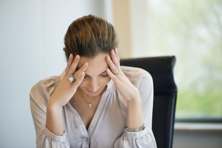 stressed woman at office with head in hands