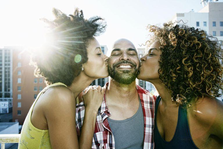 Women kissing man's cheeks on urban rooftop