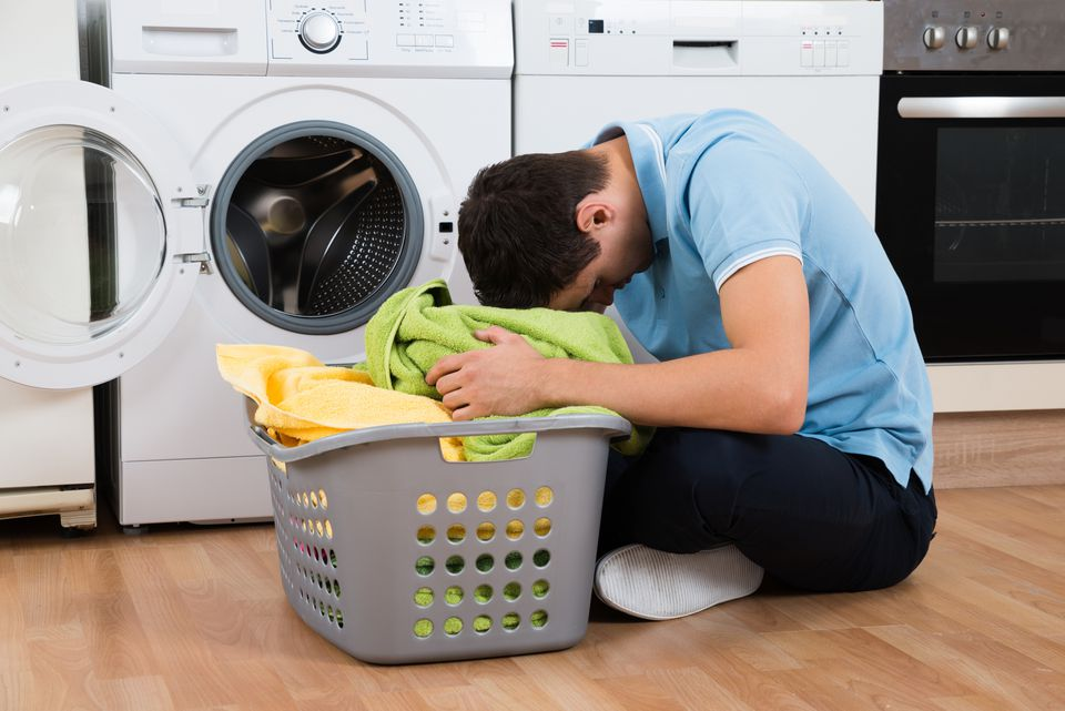 Exhausted Man With Laundry Basket Sitting By Washing Machine