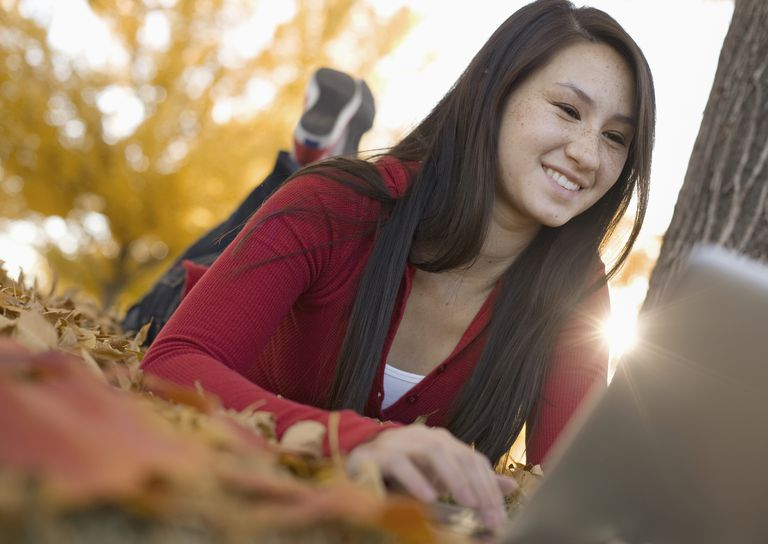 A young woman lying on the ground in autumn using a laptop computer.