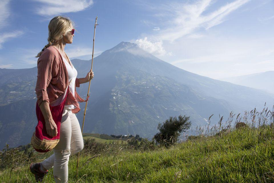 Woman walks through meadow below volcano