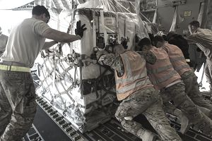 A U.S. Air Force flight line crew push a pallet of material off a C-17 cargo plane.