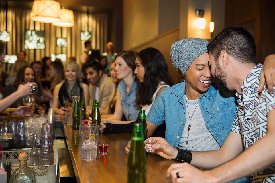 Homosexual couple hugging and drinking at bar.
