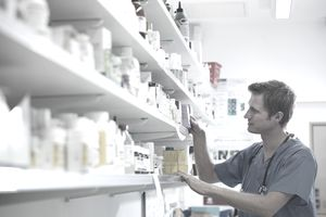 Vet selecting medications from shelf in veterinary pharmacy