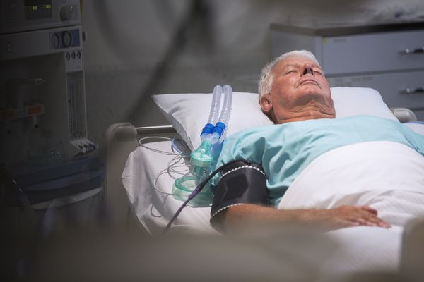 Patient lying in bed next to oxygen mask in intensive care unit