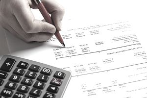 hand with pen on financial statement with calculator