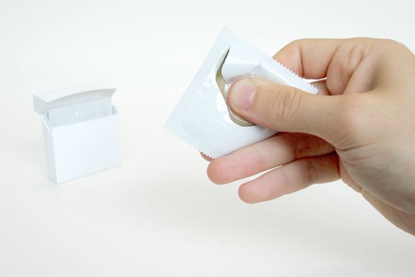 man opening condom package with one hand
