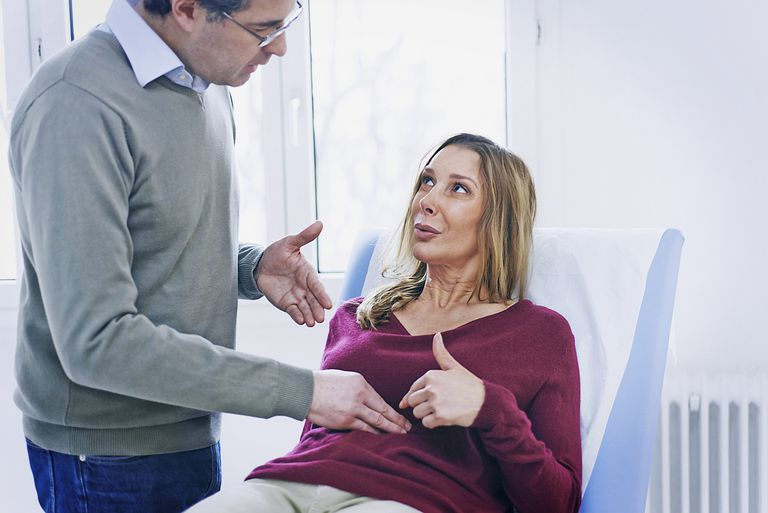 Woman talking with her doctor who is examining her abdomen.