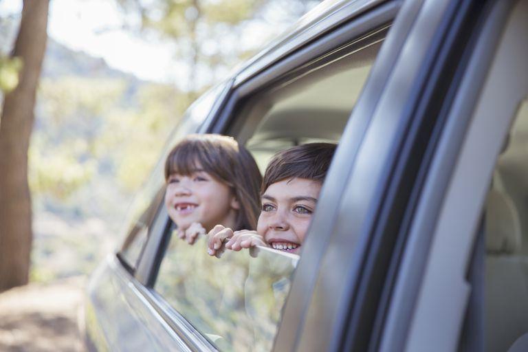 Two children looking outside of car window