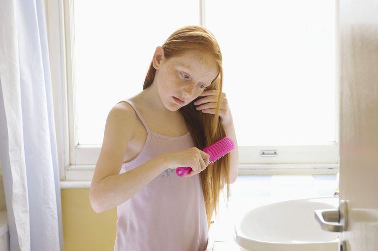 Girl (9-11) brushing long hair in bathroom