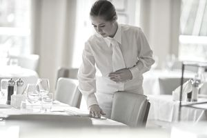 Waitress repositions flatware on restaurant table