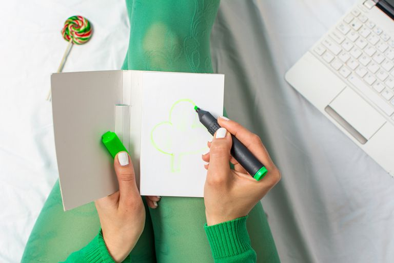 girl in green drawing a clover