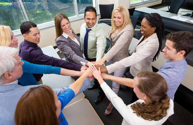 Diverse professional business team celebrates the integration of major organizational changes.
