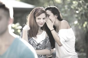 Young woman whispering secret into friend's ear