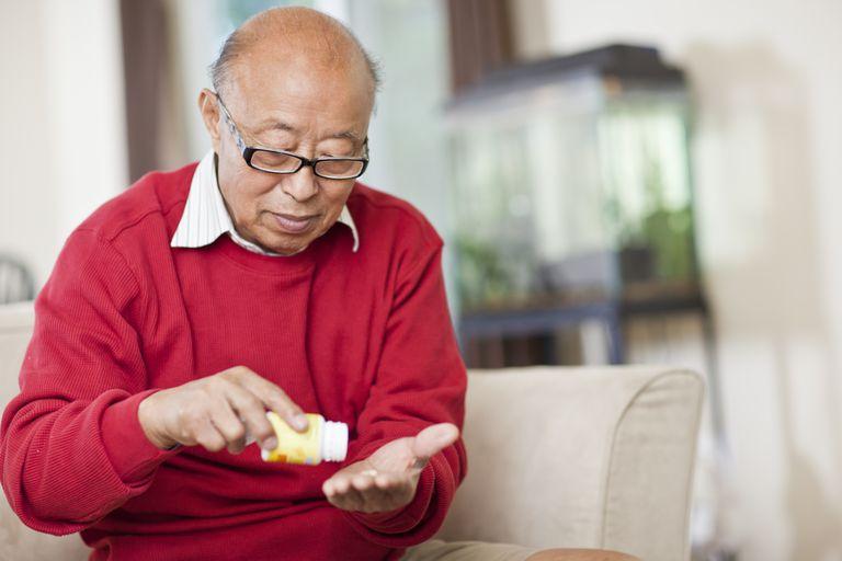 senior asian man taking medication