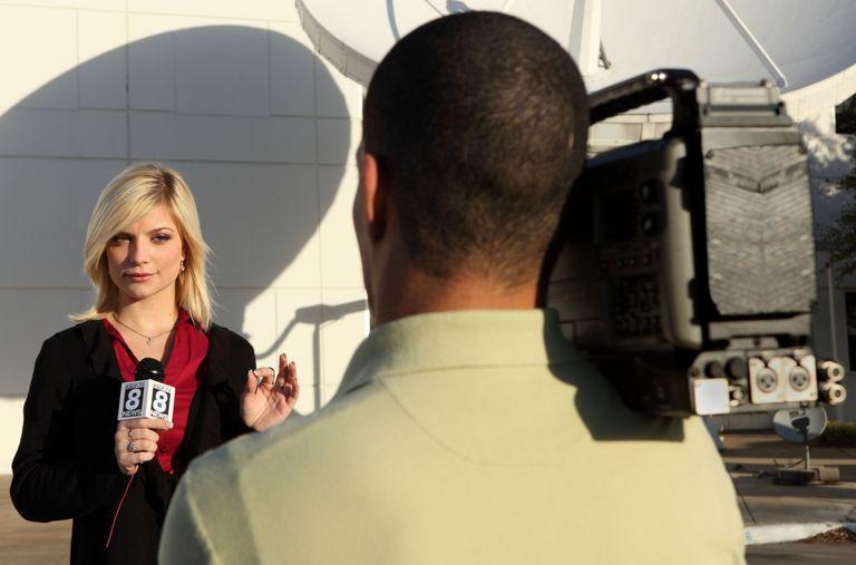 A photo of a TV news reporter preparing to talk into a camera.