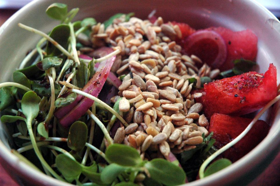 A bowl of seeds, sprouts, and watermelon