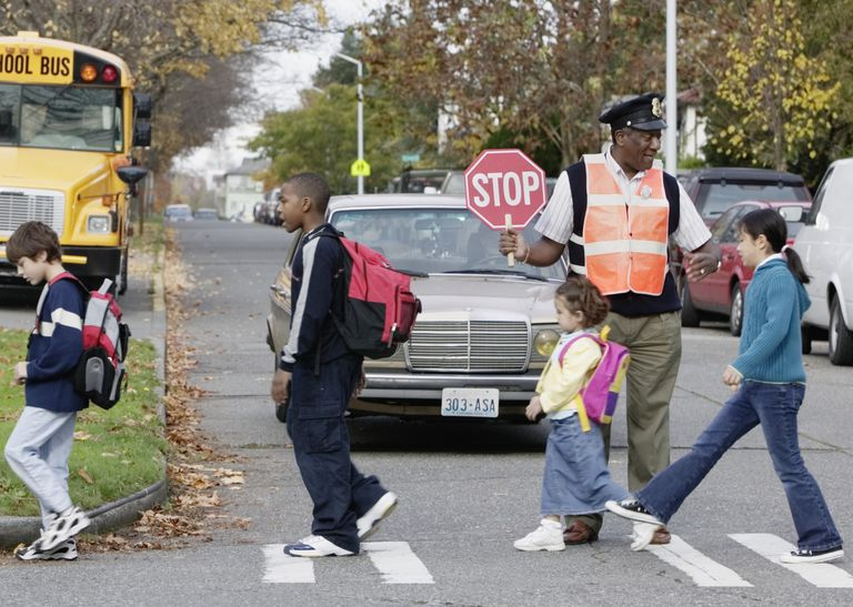 crossing guard helping children across an intersection