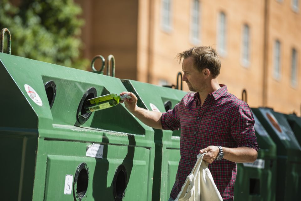 Man putting empty wine bottle into recycling bin
