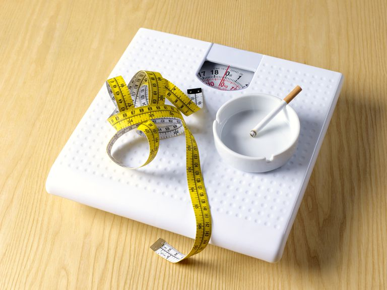 Tape measure and cigarette sitting on a scale