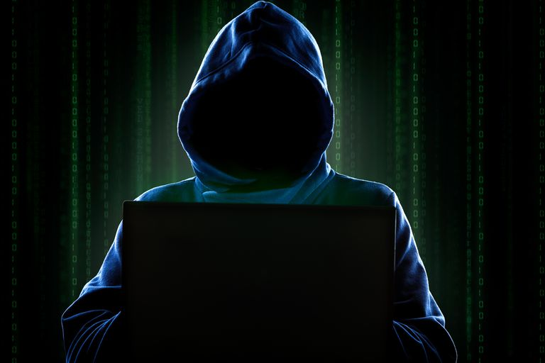 Hooded figure behind a computer