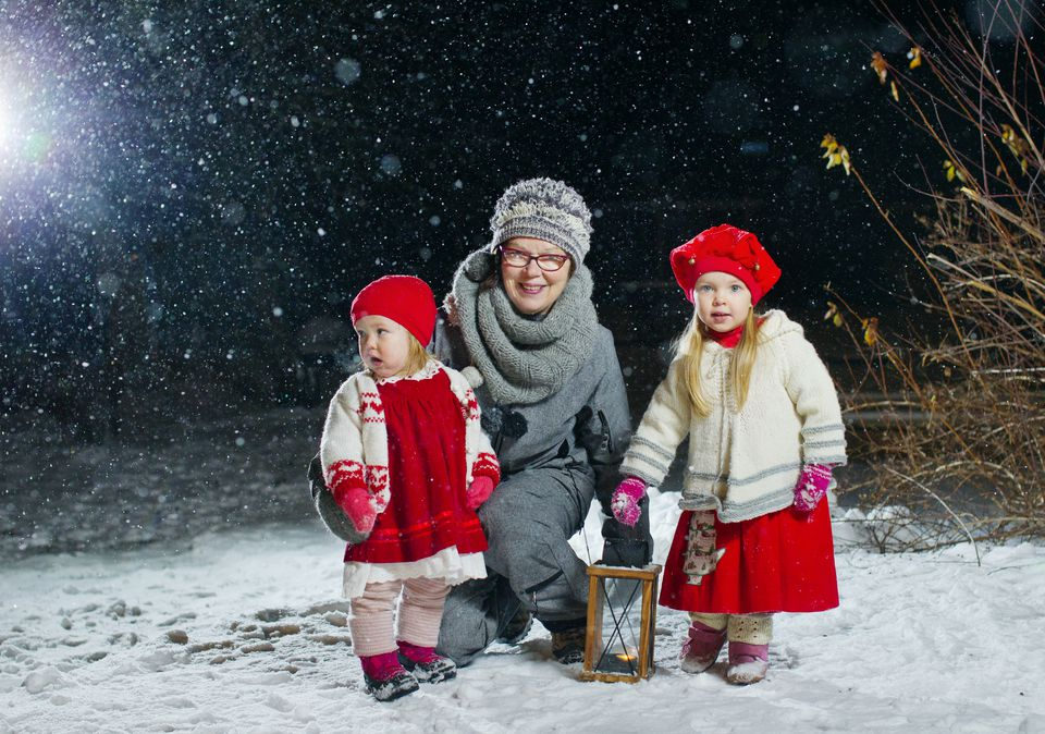 Finland, Portrait of grandmother with granddaughters (12-17 months, 2-3) in backyard at night