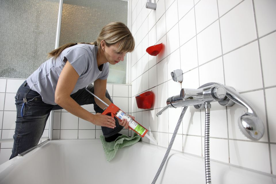 Woman Caulking Tile Around Bathtub 134469710