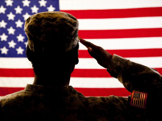 Silhouette of soldier saluting the American flag