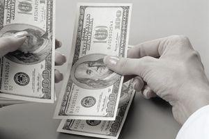 Woman counting U.S. $100 bills