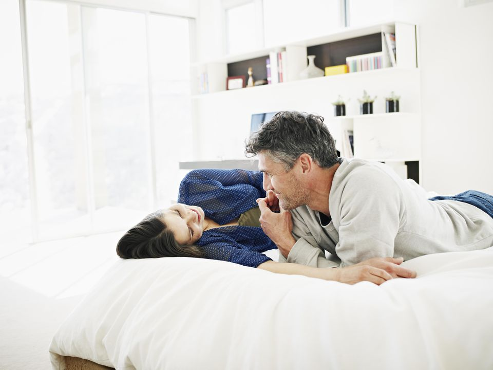 Smiling couple talking on bed in modern home
