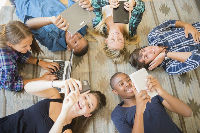Teenagers laying on floor using technology