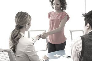 a job candidate shaking hands with a hiring manager during an interview