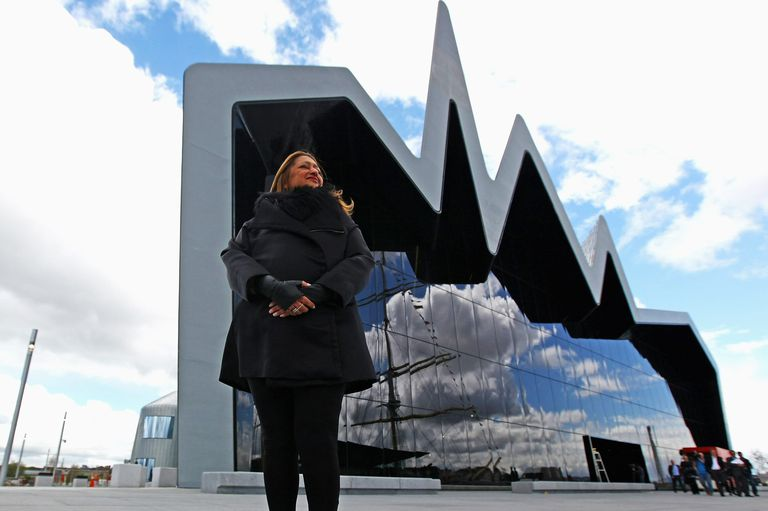 Zaha Hadid stands in front of the new Riverside Museum, jagged roof, reflective glass facade