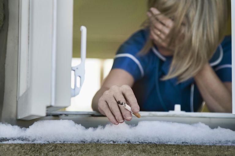 Stressed nurse smoking through an open window