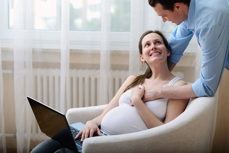 Pregnant woman sitting in chair, using laptop, husband holding her hand