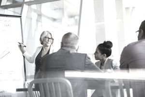 Businesswoman at whiteboard leading a meeting in conference room