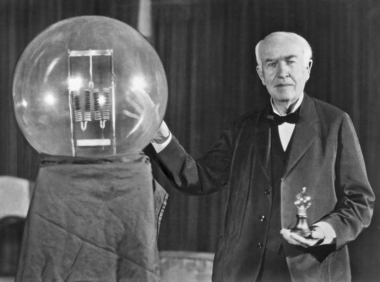 Thomas Edison stands with big bulb.