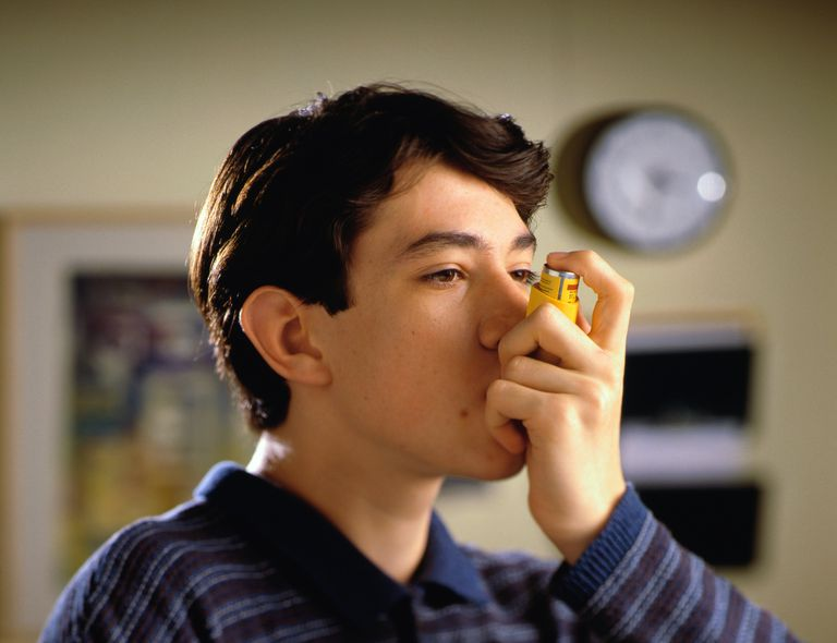 Teenage boy (14-16) using inhaler