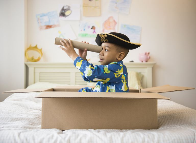 Little boy playing with cardboard box