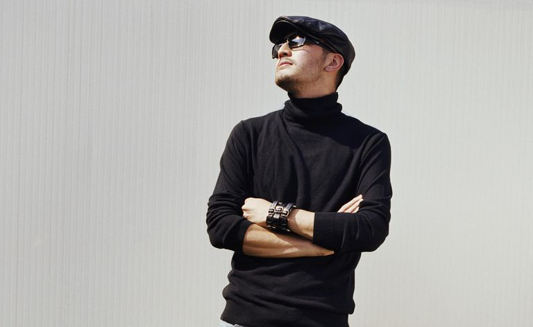 Young man wearing sunglasses looking to side, arms folded
