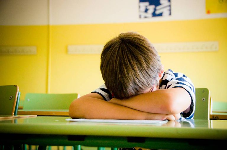 student with head down on desk