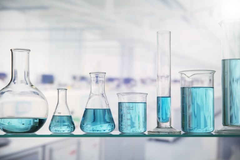 Beakers with solution on shelf in lab