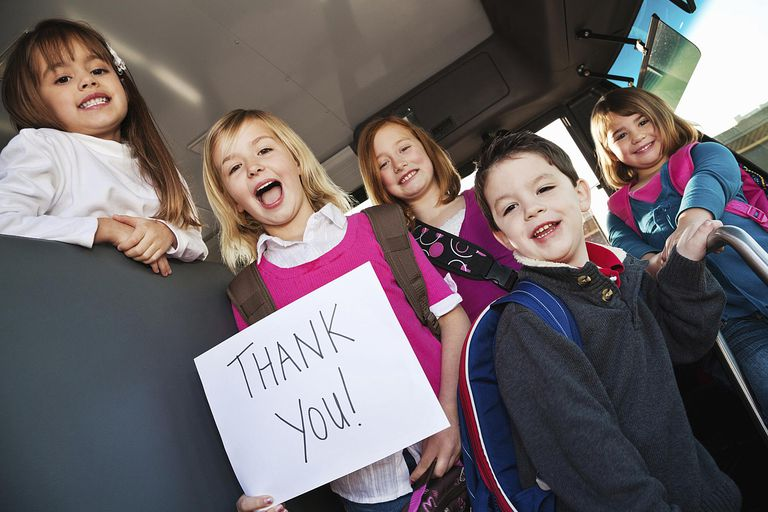 Group of grateful children holding up a thank you sign.
