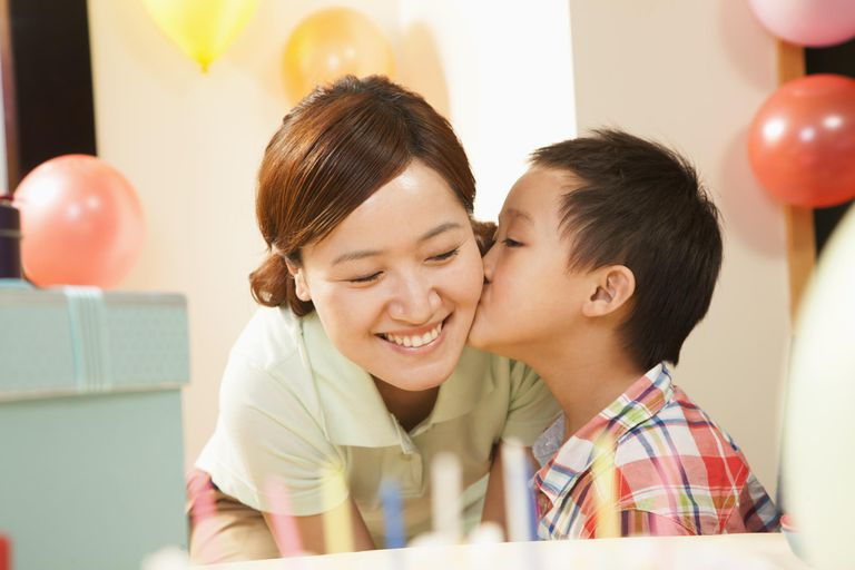 Chinese boy kissing mother at birthday party