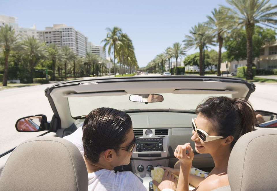Hispanic couple driving in convertible in Florida