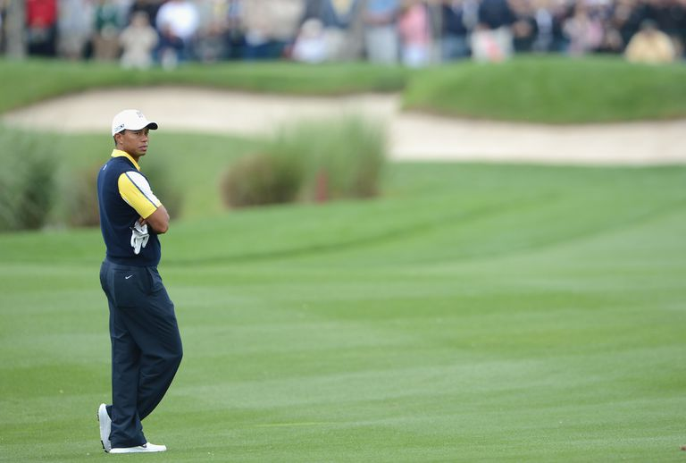Tiger Woods alone on a fairway, thinking over the next shot