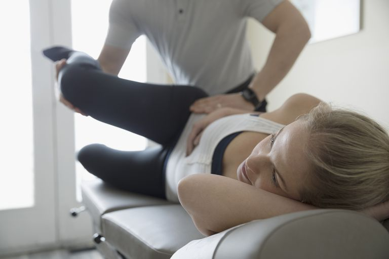 Photo of a physical therapist stretching a patient's hip.