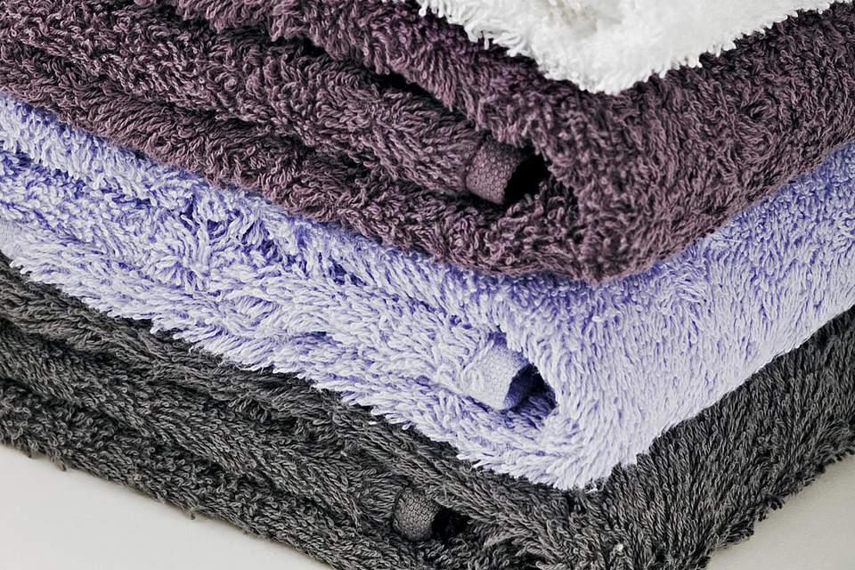 Studio shot of blue cornflowers on top of stack of towels
